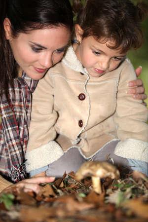 fall mushroom: Mother and daughter picking mushrooms