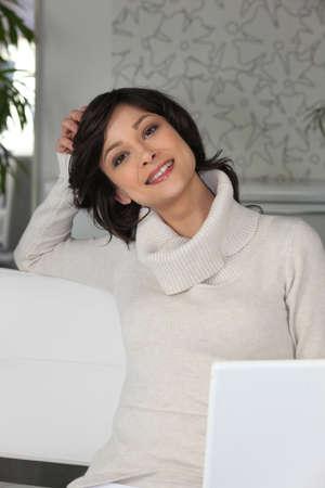beaming brunette sitting on divan home photo
