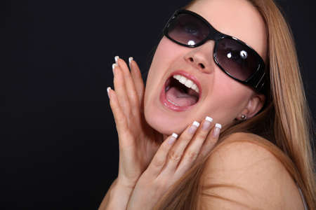 Young woman with sunglasses screaming in front of a black background photo