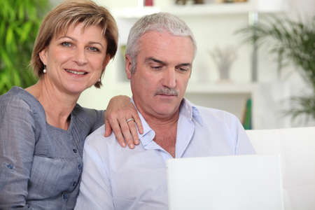 Married couple using a laptop at home photo