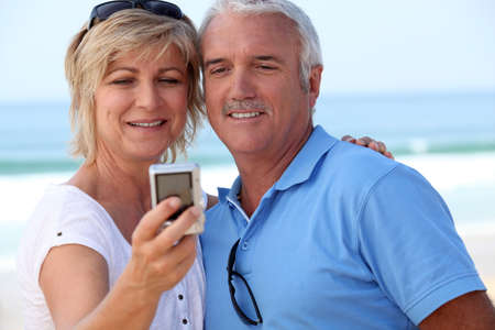 55 59 years: Mature couple taking a picture of themselves by the sea