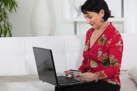 A mature woman online shopping. photo