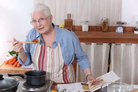 abuela: Anciana cocinar la comida con la ayuda de una receta
