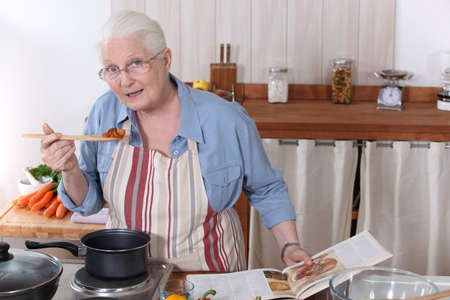 75 80: Elderly woman cooking dinner with the help of a recipe