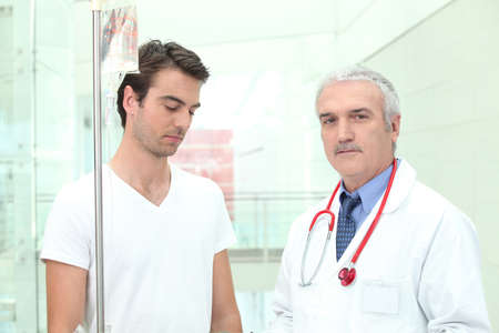 Doctor standing with a patient photo
