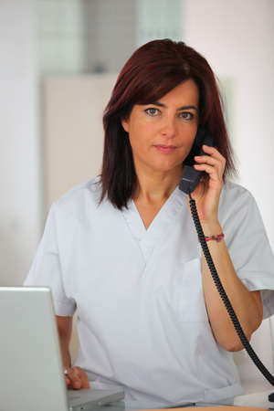 Medical secretary answering the telephone photo