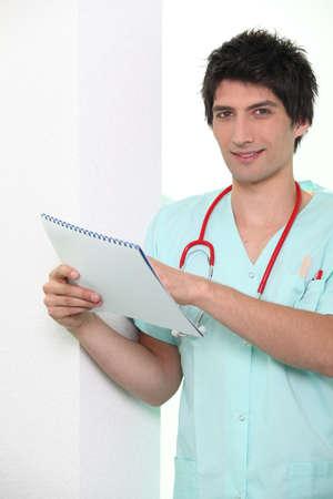 trained nurse: Male nurse holding chart