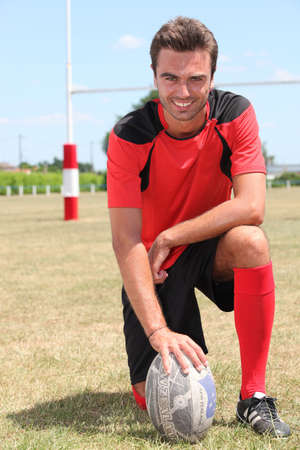 Man kneeling on rugby pitch with hand on ball photo