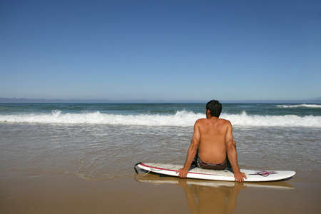 surfboard fin: Man sat on surfboard admiring the view