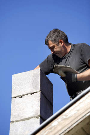 workingman: Mason building chimney Stock Photo