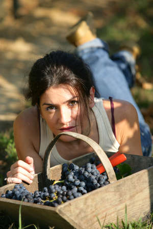 wine grower: Woman laying down with basket of grapes Stock Photo