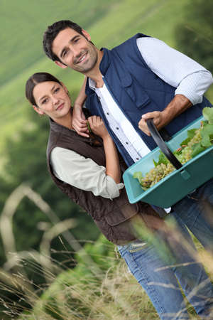Farmer couple in field with basket of grapes photo