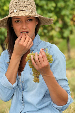 gratified: Woman eating grapes