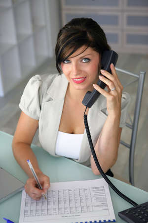Attractive secretary sitting at a desk photo