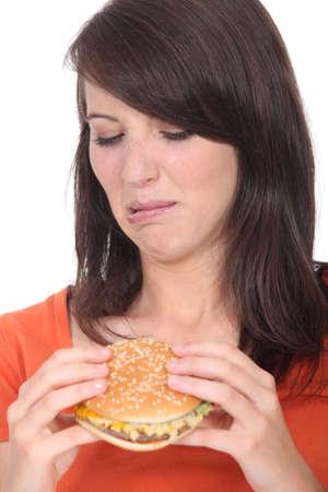sicken: Woman eating a hamburger
