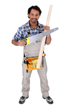 Worker holding a saw and a piece of wood photo
