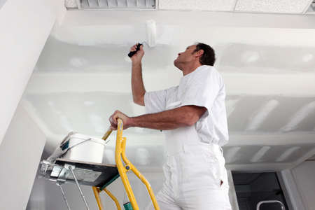 gypsum: Tradesman painting a ceiling