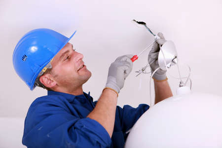 work workman: Electrician wiring a ceiling light