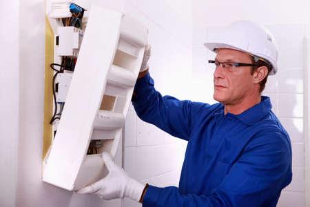 electricista: Electricista con una caja de fusibles