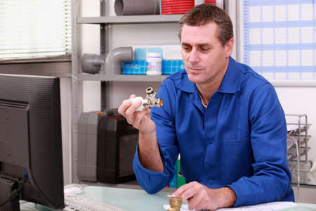 merchant: Plumber looking at a joint in a stockroom Stock Photo