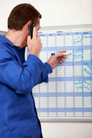 Manual worker writing names onto a wall planner photo