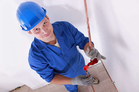 taskmaster: Smiling laborer installing piping