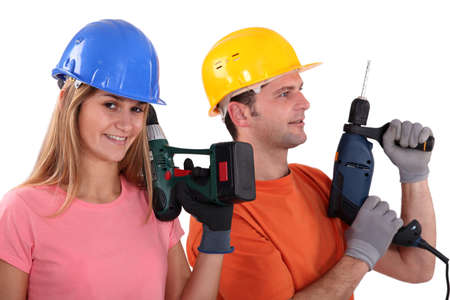 portrait of male and female workers holding electric drill photo