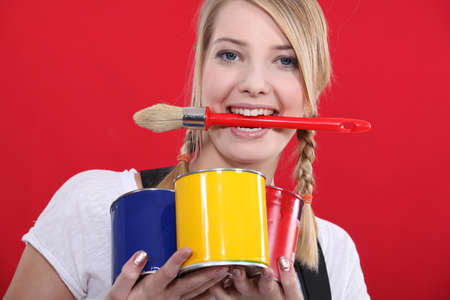 portrait of female painter holding brush between her teeth photo