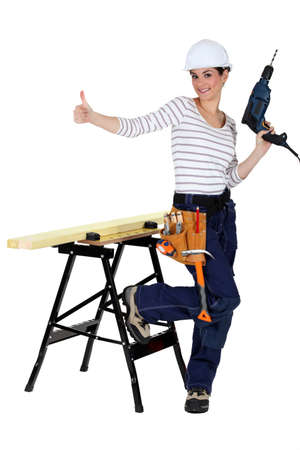 legs folded: happy-looking female carpenter thumb up Stock Photo
