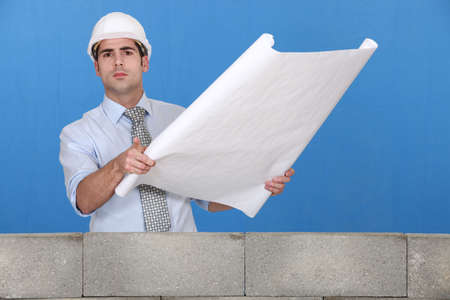 Engineer unrolling a technical drawing photo