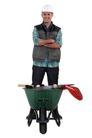 Man stood with wheelbarrow full of tools photo