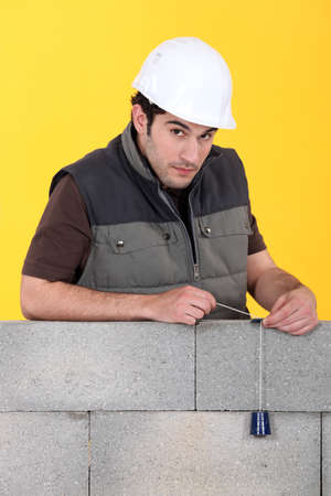 plumb: Bricklayer with a plumb line Stock Photo
