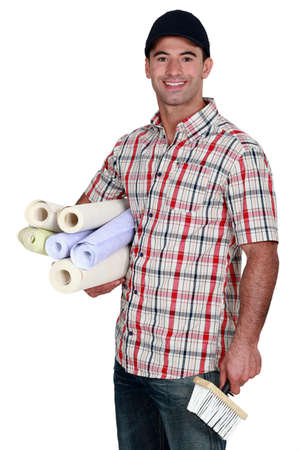 Man with rolls of wallpaper photo