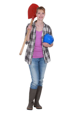 A female construction worker holding a shovel. photo
