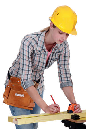 A female carpenter taking measures. photo