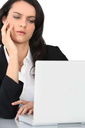 An angry businesswoman staring at her laptop