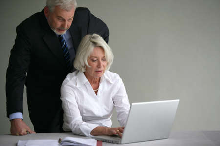 Senior couple in suit in front of a laptop computer photo