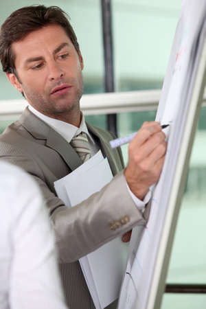 Boardroom meeting: Male executive writing on a full size flipchart