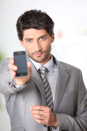 Young man showing smartphone photo