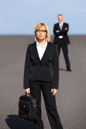Blonde businesswoman standing far apart from her colleague photo