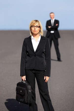 lejos: Rubia empresaria de pie lejos de su colega