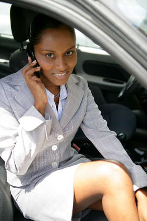 Businesswoman sat in car with mobile photo