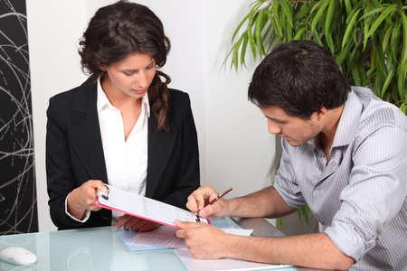administracion de empresas: Hombre joven firma de un documento Foto de archivo