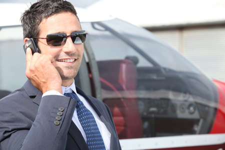 30 to 35: Businessman using a cellphone next to his private plane
