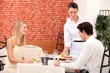 Waitress serving a young couple in a restaurant photo