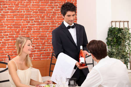 alcohol server: Young couple choosing rose wine in a restaurant