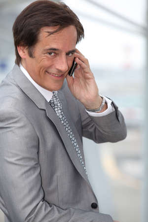 Businessman smiling on mobile phone Stock Photo - 12089635