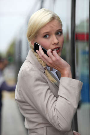 blonde woman at phone having an anxious face expression photo