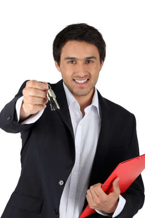 Estate-agent holding keys and folder Stock Photo - 12088658