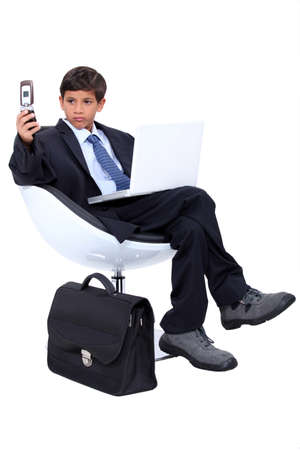 grown ups: Young boy dressed as a surly businessman